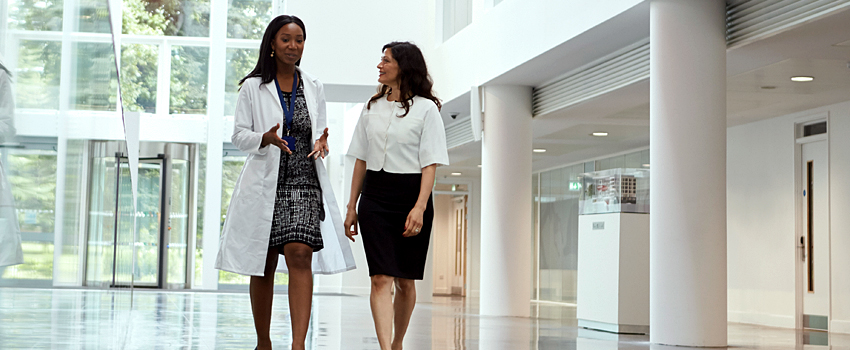 Two female physicians having conversation as they walk down the hallway of a hospital