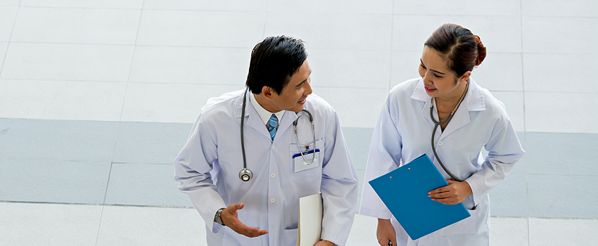 A male and female physician walk next to eachother as they discuss something