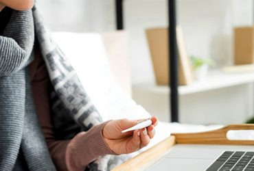Woman sitting down on couch with large scarf around her neck checks themometer as she looks at her laptop screen.