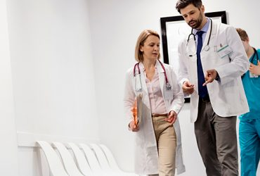 One male and one female physician walk down the hallway while having a discussion