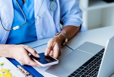 Female physician with stethescope around neck sitting at desk with laptop while checking her cellphone.