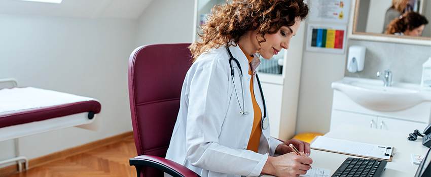 Female physician with curly hair fills out paperwork in front of computer while sitting in her office