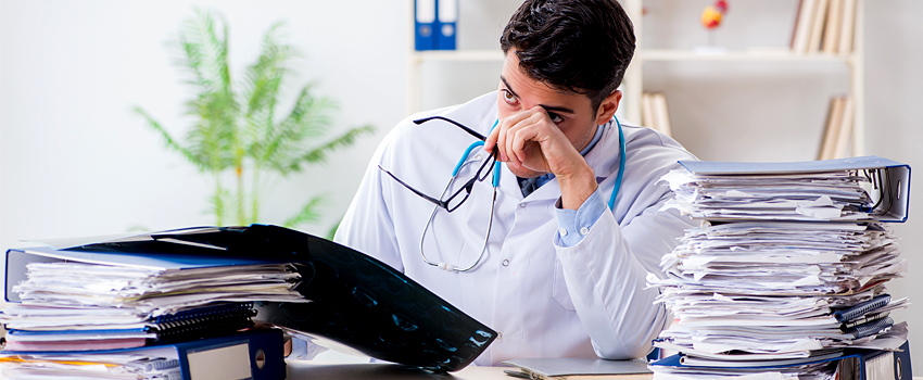 Tired, young male physician sitting at desk with head in his hand surrounded by paperwork