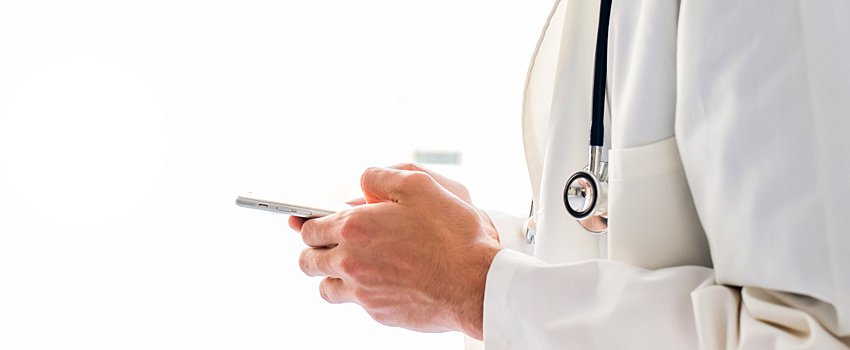 Midsection of male physician looking down at smartphone in their hands