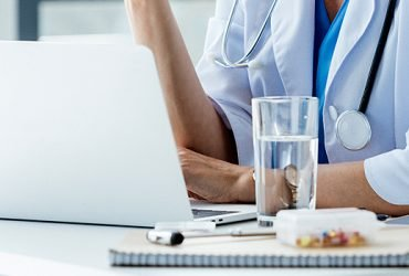 Close-up photo of physician sitting at desk with laptop