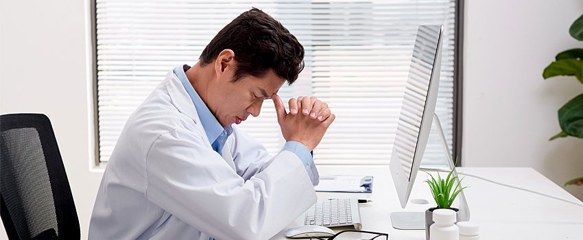 Male physician with head in hands experiencing physician burnout