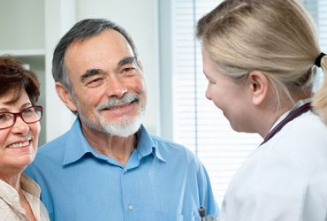 Physician smiling with satisfied patients