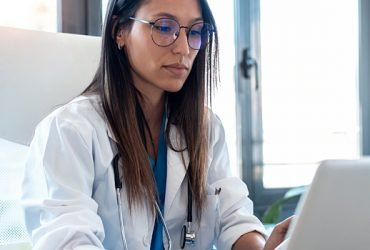 Female physician working on laptop at desk